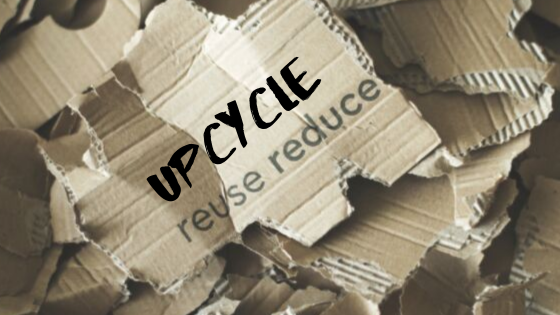 Pieces of cardboard that say reduce, reuse, and upcycle.